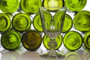 Leeres Weinglas vor Weinflaschen vor weißem Hintergrund